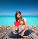 Happy mother with adorable little girl and heart. Childhood, parenting and relationship concept - happy mother with adorable little girl and red heart Royalty Free Stock Images