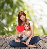 Happy mother with adorable little girl and heart. Childhood, parenting and relationship concept - happy mother with adorable little girl and red heart Royalty Free Stock Photography