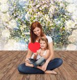 Happy mother with adorable little girl and heart. Childhood, parenting and relationship concept - happy mother with adorable little girl and red heart Royalty Free Stock Photos