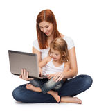 Happy mother with adorable little girl and laptop. Childhood, parenting and technology concept - happy mother with adorable little girl with laptop Royalty Free Stock Images