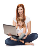 Happy mother with adorable little girl and laptop. Childhood, parenting and technology concept - happy mother with adorable little girl with laptop Royalty Free Stock Image