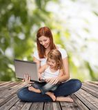 Happy mother with adorable little girl and laptop Royalty Free Stock Photo