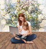 Happy mother with adorable little girl and laptop Royalty Free Stock Image