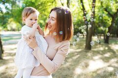 Free Happy Mother And Daughter Blowing Bubbles In The Park Stock Photos - 217352443