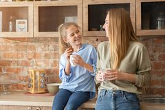 Free Happy Mother And Daughter Drinking Tea At Kitchen Stock Images - 160322034