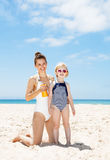 Happy mother applying sunscreen on child in swimsuit at beach Royalty Free Stock Photos