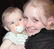 Happy Mother with Baby. Gorgeous, smiling, blonde woman embraces cute blue eyed baby boy with binky in his mouth Royalty Free Stock Photography