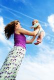 Happy mother and baby. A happy mother raises her baby up in the air Royalty Free Stock Image