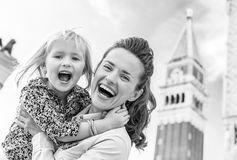 Happy mother and baby against campanile di san marco in venice, stock photo