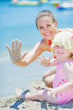 Happy mother and baby on beach greeting Stock Photography