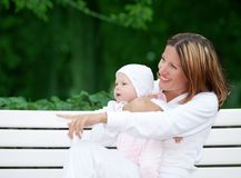 Happy mother with baby on the bench Royalty Free Stock Image
