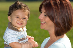 Happy mother with baby boy. Side portrait of happy mother with baby boy outdoors Stock Photos