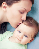 Happy Mother With Baby Boy. Baby boy with beautiful blue eyes being kissed by his mother stock photos