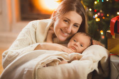 Happy mother and baby boy in blanket posing in Christmas room Stock Photos