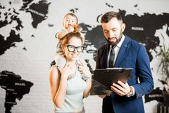 Happy family with travel agent at the office. Happy mother and baby boy choosing tour for a summer vacation with male agent at the travel agency office with Stock Photography