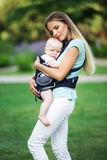 Happy mother with baby boy in sling walking in park Royalty Free Stock Image