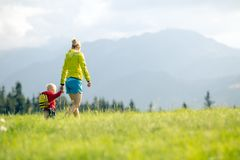 Happy mother with baby boy walking on green meadow royalty free stock photography