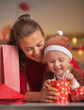 Happy mother and baby checking christmas purchases Royalty Free Stock Image