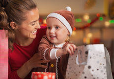 Happy mother and baby checking christmas shopping bags Royalty Free Stock Photos