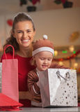 Happy mother and baby checking christmas shopping bags Stock Photos