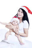 Happy mother and baby in christmas hats Royalty Free Stock Photo