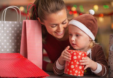 Happy mother and baby among christmas shopping bags Stock Images