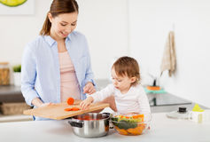 Happy mother and baby cooking food at home kitchen. Family, food, healthy eating, cooking and people concept - happy mother with chopped carrot and little baby Stock Photos