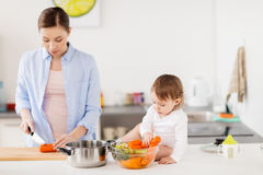 Happy mother and baby cooking food at home kitchen. Family, food, healthy eating, cooking and people concept - happy mother chopping carrot and little baby girl Stock Photography