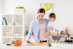 Happy mother and baby cooking food at home kitchen. Family, food, healthy eating, cooking and people concept - happy mother chopping carrot and little baby girl Stock Photos