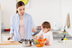 Happy mother and baby cooking food at home kitchen. Family, food, healthy eating, cooking and people concept - happy mother and little baby girl with vegetables Stock Photography