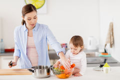 Happy mother and baby cooking food at home kitchen. Family, food, healthy eating, cooking and people concept - happy mother and little baby girl with vegetables Royalty Free Stock Photos
