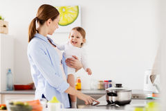 Happy mother and baby cooking at home kitchen. Family, food, healthy eating and people concept - happy mother and little baby girl cooking dinner together at Royalty Free Stock Images
