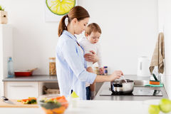 Happy mother and baby cooking at home kitchen. Family, food, healthy eating and people concept - happy mother and little baby girl cooking dinner together at Stock Image