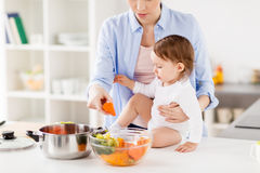 Happy mother and baby cooking vegetables at home. Family, food, healthy eating, cooking and people concept - happy mother and little baby girl with vegetables Royalty Free Stock Photography