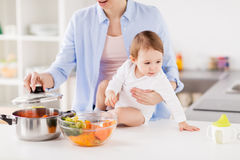 Happy mother and baby cooking vegetables at home. Family, food, healthy eating, cooking and people concept - happy mother and little baby girl with vegetables Stock Photography