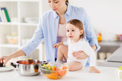 Happy mother and baby cooking vegetables at home. Family, food, healthy eating, cooking and people concept - happy mother and little baby girl with vegetables Royalty Free Stock Photo