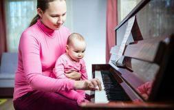 Happy Mother And Baby Daughter Are Playing Piano Royalty Free Stock Images