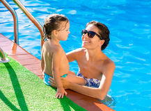 Happy mother and baby daughter swimming pool. Happy mother and baby daughter girl at swimming pool in summer vacation royalty free stock photography