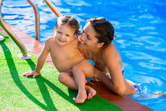 Happy mother and baby daughter swimming pool. Happy mother and baby daughter girl at swimming pool in summer vacation royalty free stock photo