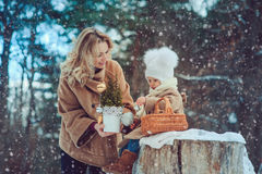 Happy mother and baby daughter walking in snowy winter park Royalty Free Stock Photos