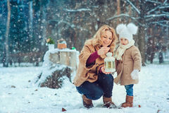 Happy mother and baby daughter walking in snowy winter park Stock Image