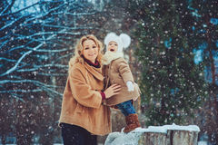 Happy mother and baby daughter walking in snowy winter park Stock Photo