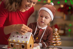 Happy mother and baby decorating christmas cookie house. In kitchen stock photos