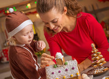 Happy mother and baby decorating christmas cookie house Royalty Free Stock Photo