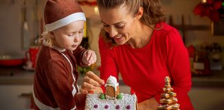 Mother and baby decorating christmas cookie house Royalty Free Stock Photography