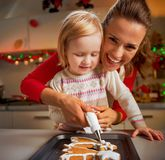 Mother and baby decorating homemade christmas cookies with Royalty Free Stock Photos
