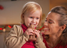 Happy mother and baby eating chocolate santa Royalty Free Stock Images