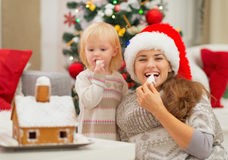 Happy mother and baby eating Christmas cookies Royalty Free Stock Images