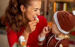 Mother and baby eating cookie in christmas decorated kitch Royalty Free Stock Photo