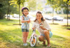 Happy mother and baby girl with bicycle Stock Images
